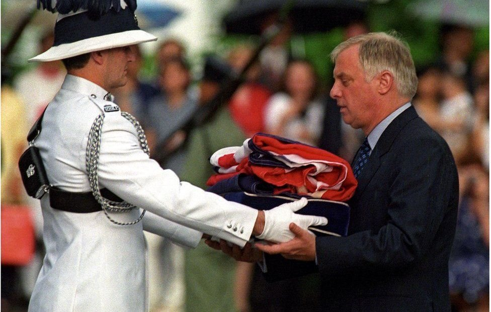 El último gobernador de Hong Kong, Chris Patten, recibe la bandera británica