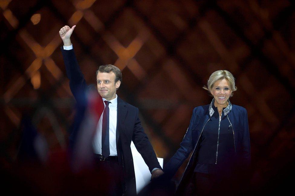 El presidente electo francés Emmanuel Macron y su mujer Brigitte Trogneux saludan a sus seguidores en frente de la Pirámide del Museo del Louvre Museum en París.