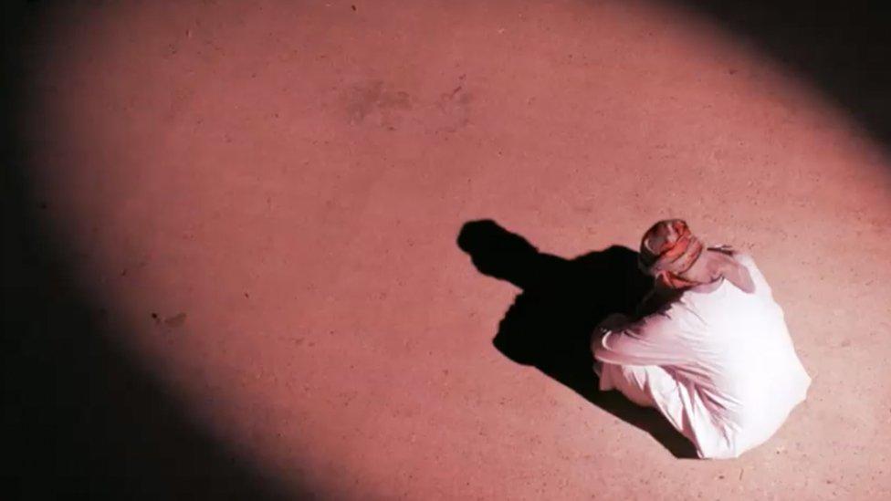 Hombre árabe sentado mirando hacia abajo
