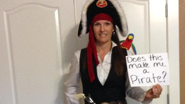 A woman dressed as a pirate with a message reading 'does this make me a pirate?'