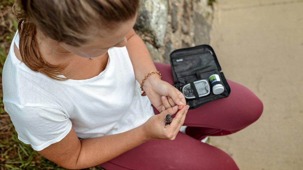 Mujer midiéndose el nivel de azúcar en la sangre.