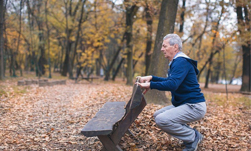 Hombre mayor haciendo sentadillas.