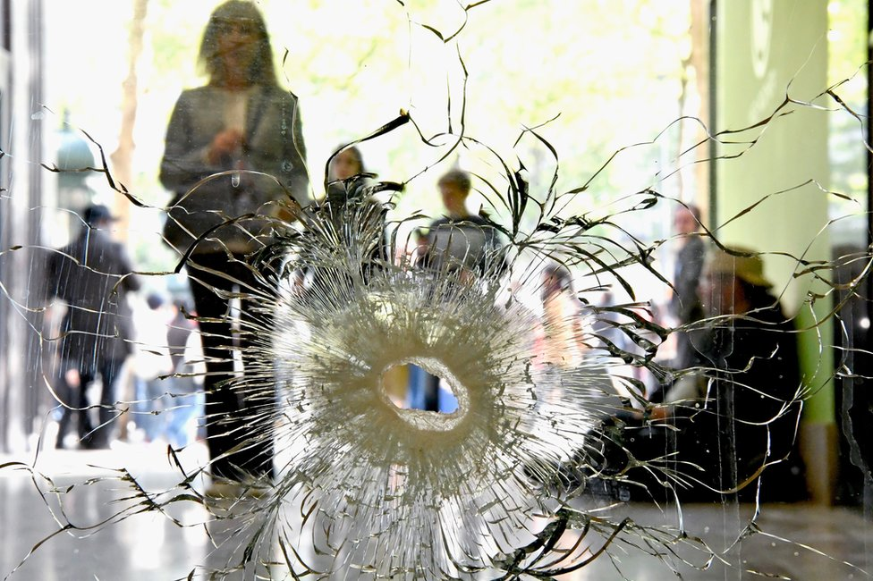 People look at a bullet hole in a window near to the Marks and Spencer on the Champs Elysees in Paris following the shooting of a police officer, 21 April