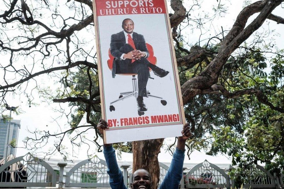 رجل من عاصمة كينيا، نيروبي، يحمل لافتة للرئيس أوهورو كينياتا بعدما أيدت محكمة نتائج إعادة الانتخابات الرئاسية الشهر الماضي المثيرة للجدل والتي أثارت انقاسامات عميقة في المجتمع الكيني، الأمر الذي يعبد الطريق أمامه لأداء اليمين الدستورية الأسبوع المقبل لولاية ثانية.