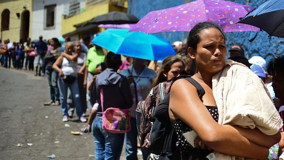 Las largas colas para adquirir alimentos son una escena repetida afuera de los mercados de Venezuela dada la escasez que vive el país.