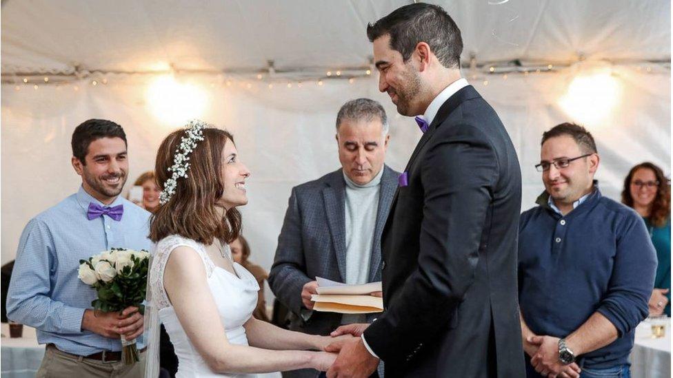 Nicole y Danny Rios se cogen de las manos y se ríen mientras se casan. Foto: Stephanie Scapellati.