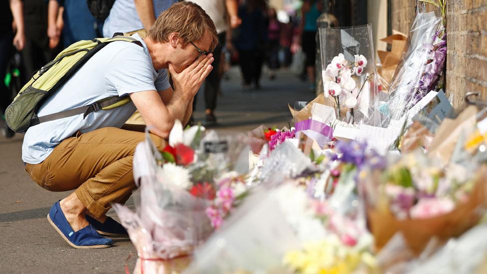 Joven mostrando consternación frente a flores dejadas por el público tras el ataque