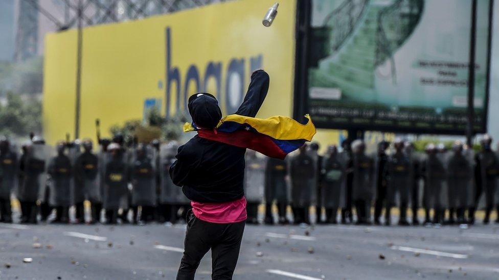 Una manifestante lanza un objeto