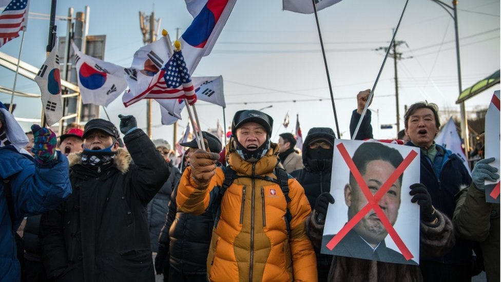 Protestors holding US and South Korean flags, and a sign with Kim Jong-Un's face crossed out.
