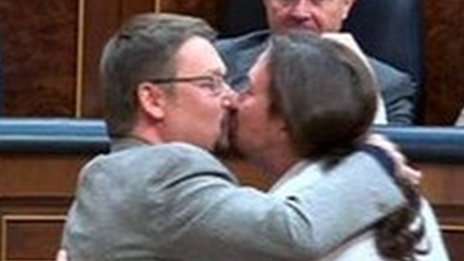 """Translation: """"You have to admit that the best part of this kiss between Pabloe Iglesias and Xavier Domenech is the looks on the faces of the PP"""" - the politicians from the conservative Popular Party who are looking on"""