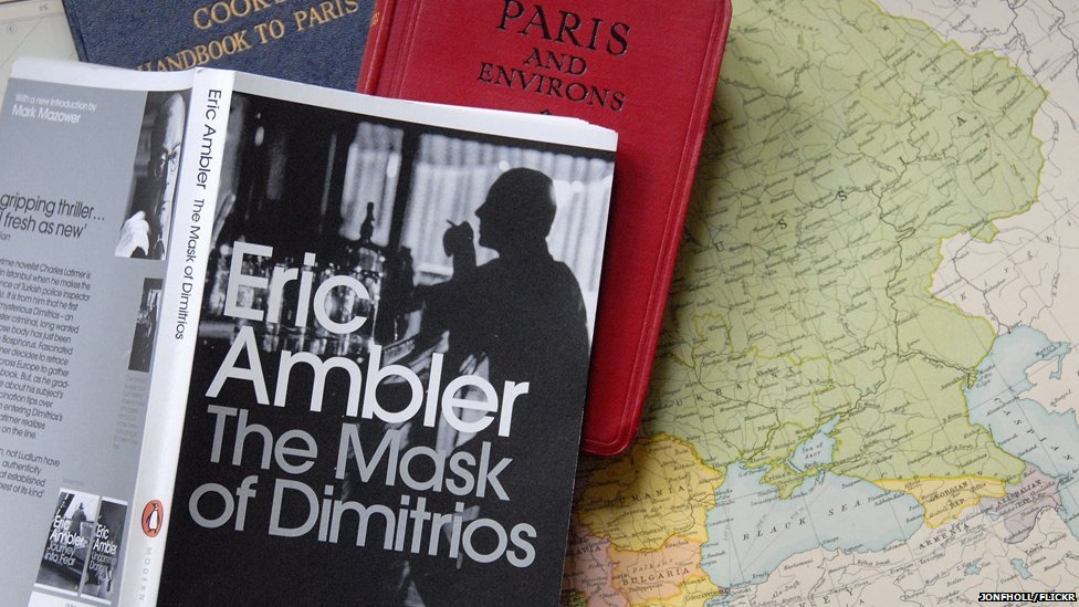 Copy of The Mask of Dimitrios sitting on vintage guide book to Paris and European map