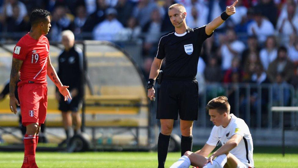 Un árbitro regaña a un jugador peruano mientras uno neozelandés está en el suelo