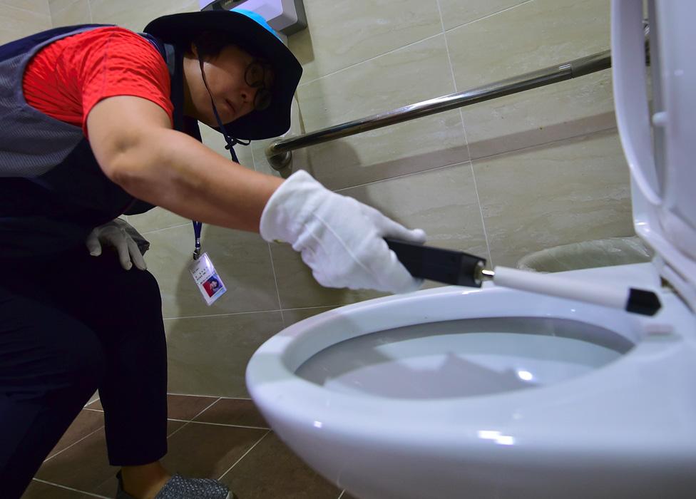 Una integrante del escuadrón en Seúl inspecciona los baños de mujeres
