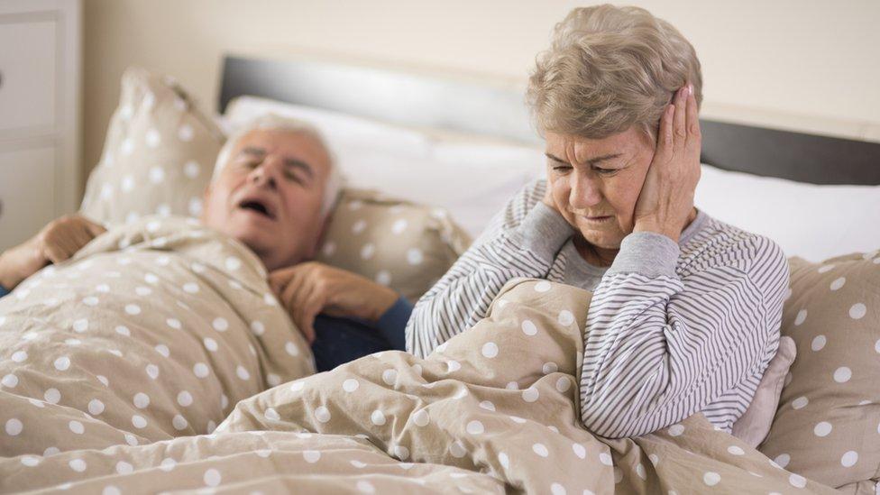 Mujer mayor se tapa los oídos mientras el hombre que tiene junto a ella en la cama ronca.