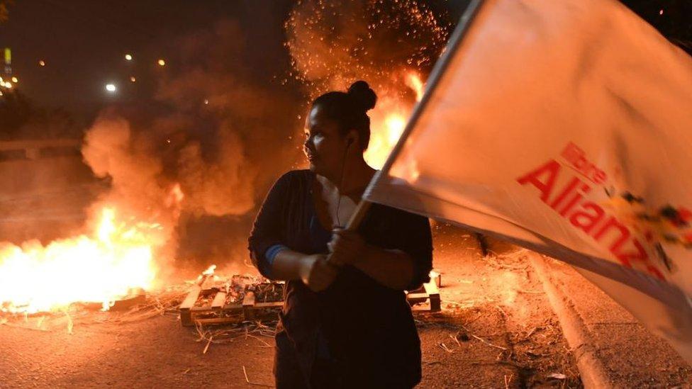 Mujer con una bandera que dice Libre Alianza