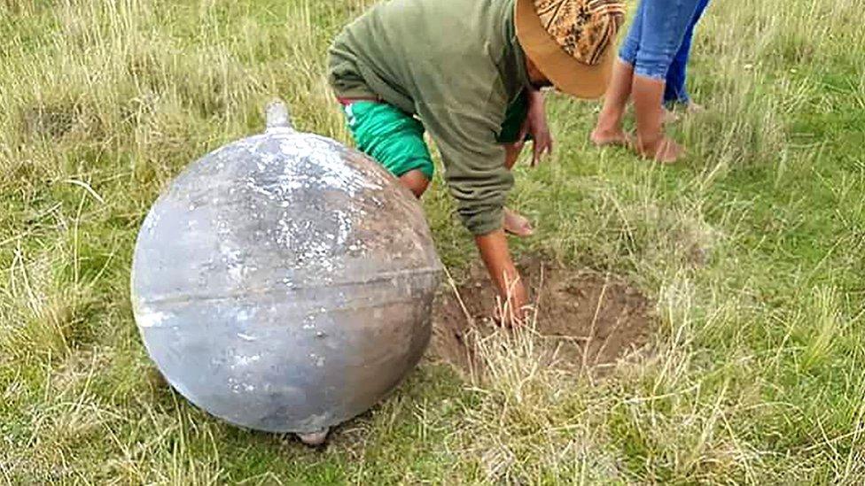Un hombre señala el hueco que abrió en la tierra el objeto que cayó del cielo en la provincia peruana de Azángaro.
