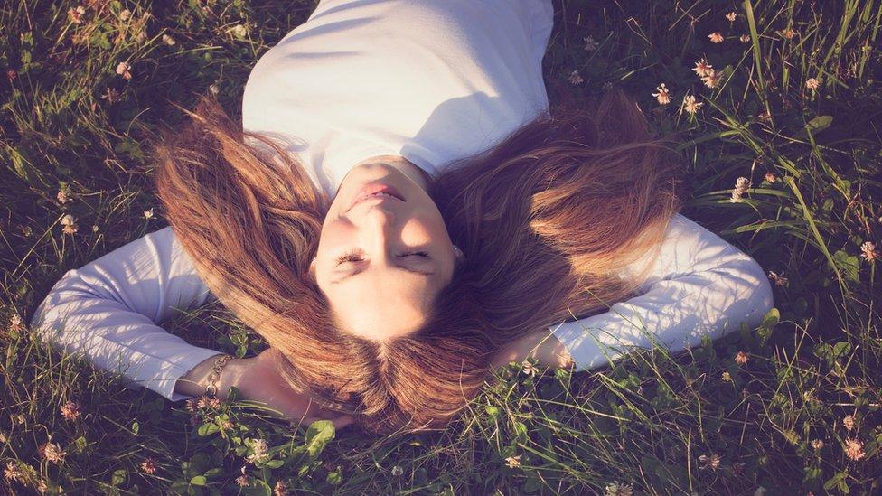 Una mujer echada en el pasto