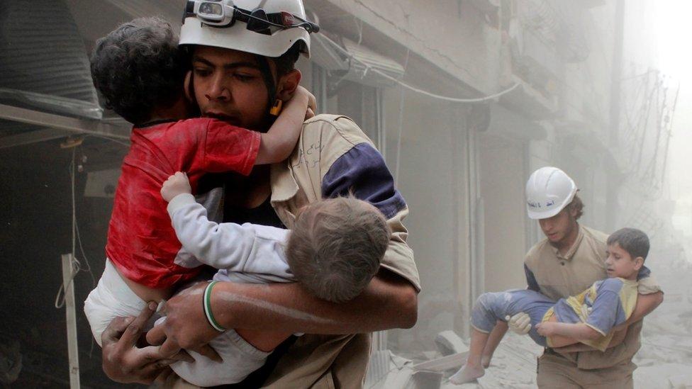 Rescatistas cargando niños en una bombardeada Alepo.