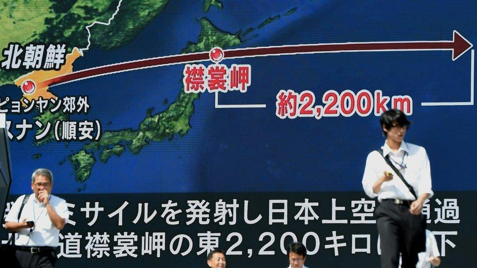 Ciudadanos caminan frente a una gran pantalla en Japón que muestra la trayectoria del último misil norcoreano.
