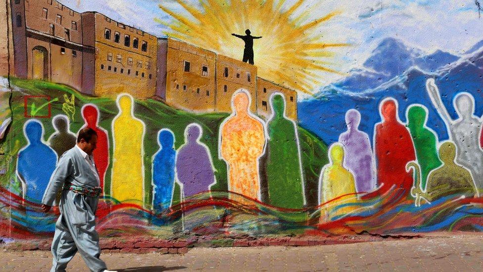 رجل كردي يسير قرب صورة ملونة مرسومة على حائط