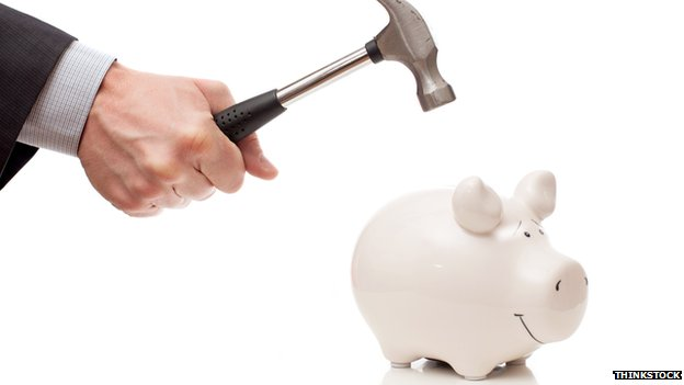 man with hammer and piggy bank