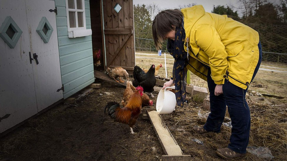 Claire en su granja con gallinas y patos
