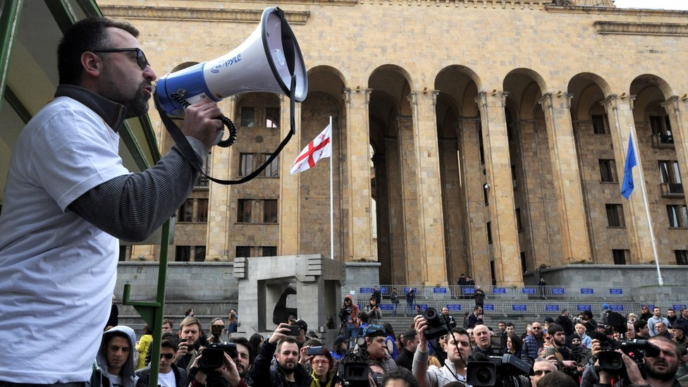 A Georgian opposition supporter shouts slogans during a protest rally against the sex tape leaks