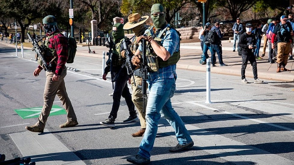 Armed groups cross the street as they hold a rally in front of a closed Texas State Capitol in Austin, Texas