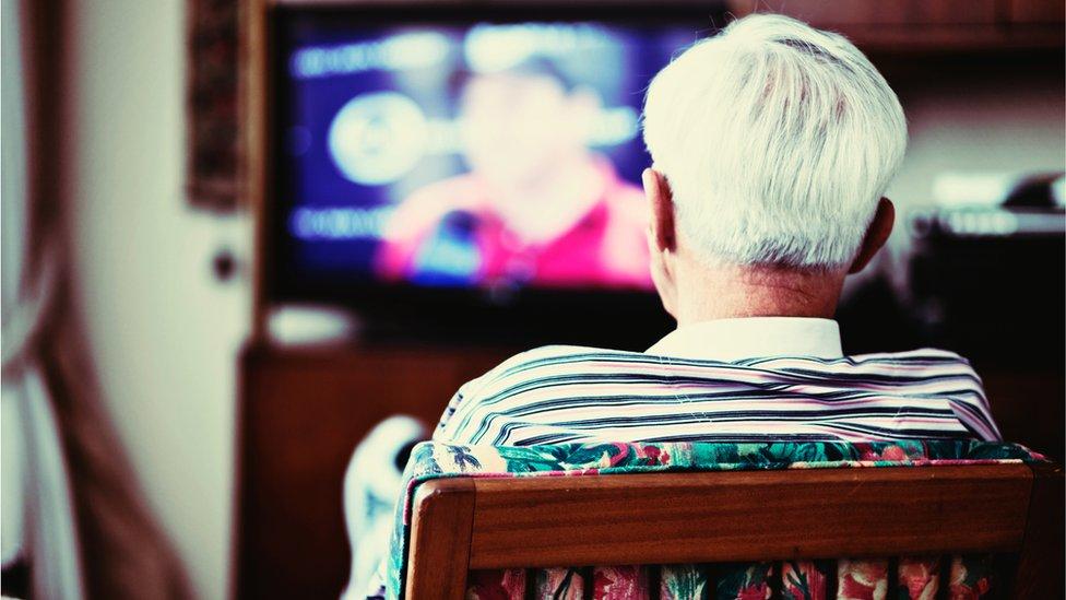 Hombre solitario viendo la televisión.