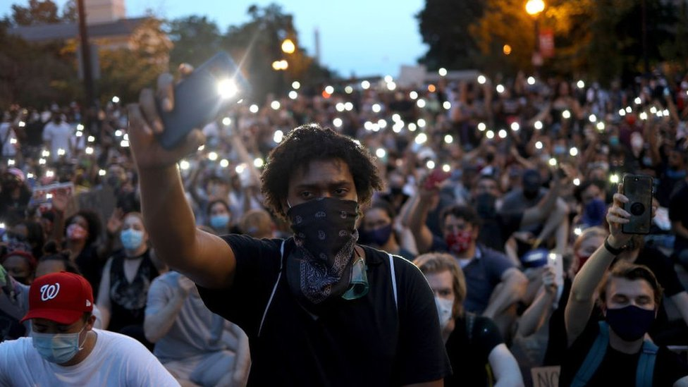 "Demonstrators sing ""Lean On Me"" near the White House during a peaceful protest against police brutality and the death of George Floyd, on June 3, 2020 in Washington, DC"