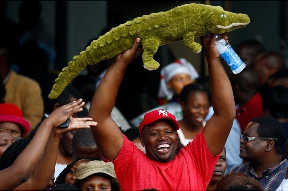 رجل يحمل صورة تمساح للترحيب بالرئيس إيمرسون منانغاغوا المعروف باسم