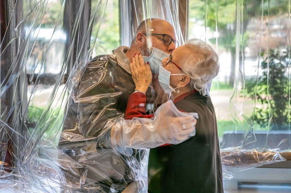A care 香港集運王 resident kisses their relative through a plastic sheet