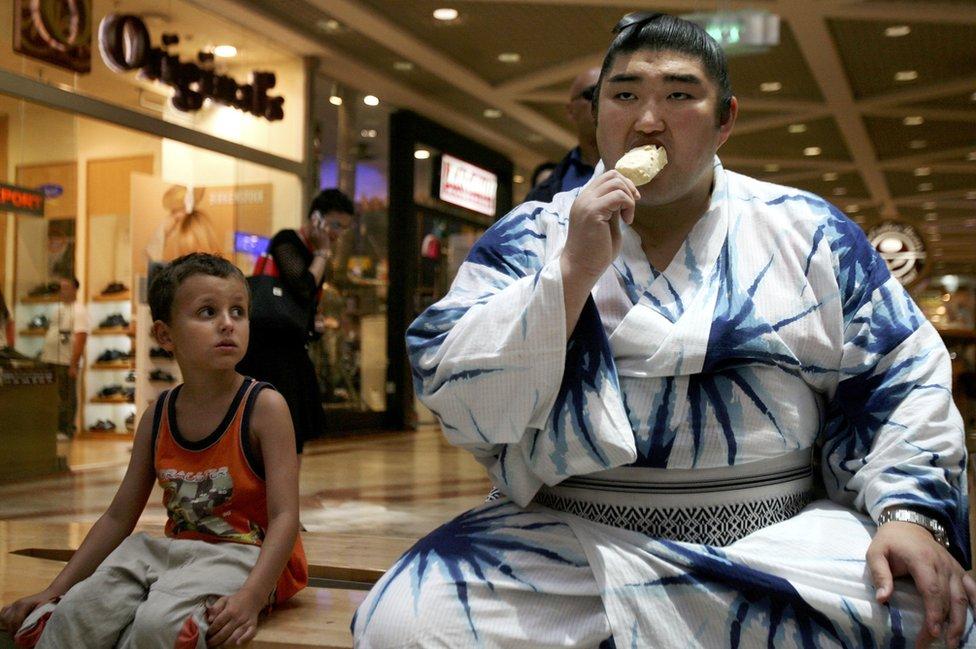 Luchador de sumo tomando un helado con su vestimenta tradicional. ((Foto: Uriel Sinai/Getty Images)