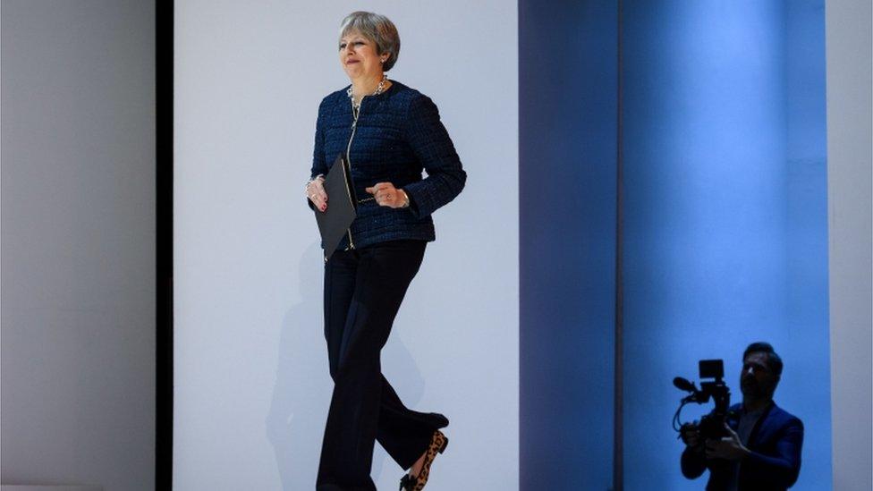 Theresa May walks onto the stage at Davos