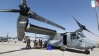 US soldiers stand in the shade of the wing of a Bell Boeing V-22 Osprey, a , tiltrotor military aircraft, at the Dubai Airshow on 8  Nov, 2015