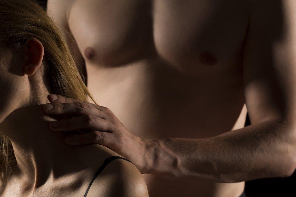 Hombre con torso desnudo toca el cuello a una mujer.