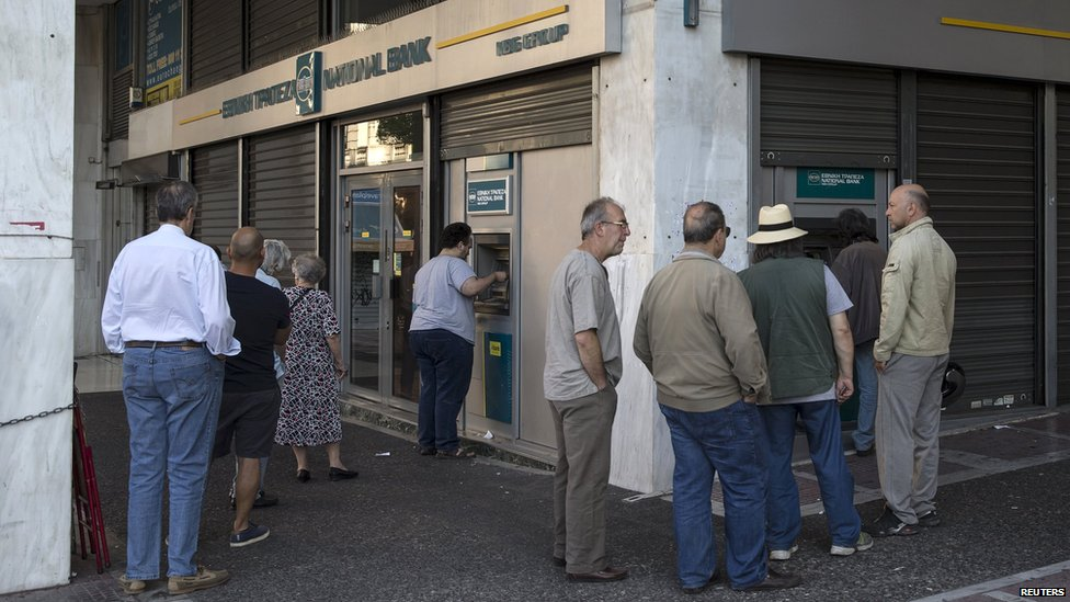 People line up at ATMs outside a National Bank branch in Athens, Greece, on 28 June 2015