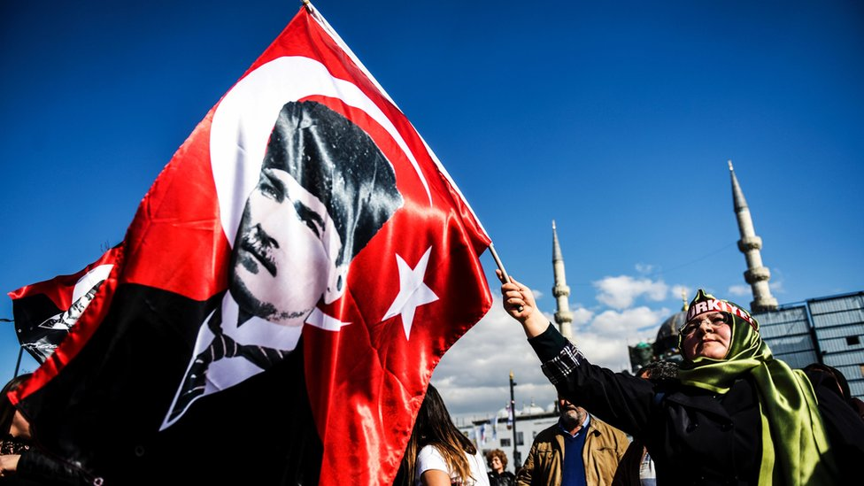 سيدة تحمل علما يحمل صورة أتاتورك مؤسس تركيا الحديثة