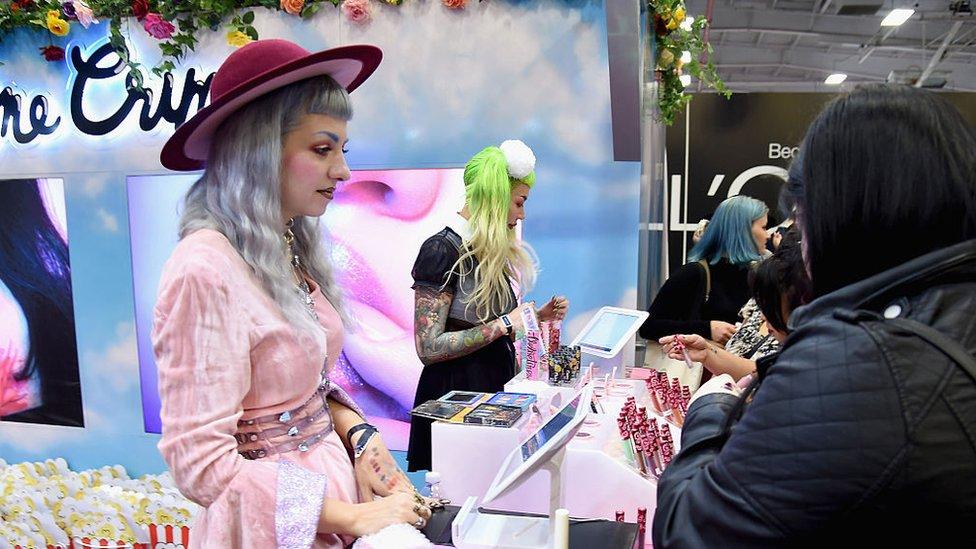 """La joven del vestido rosado lleva el cabello pintado de color """"unicornio""""."""