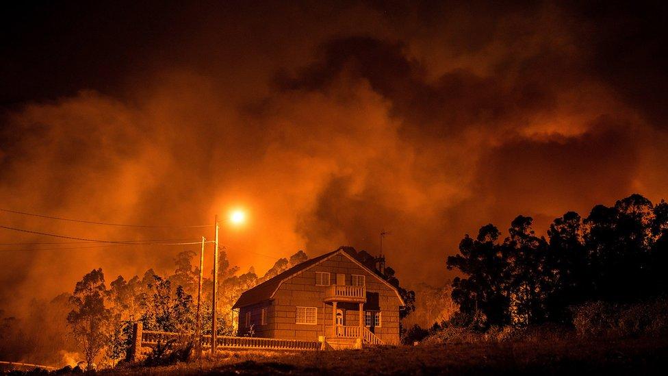 El fuego arde cerca de una casa en Nigrán, Galicia