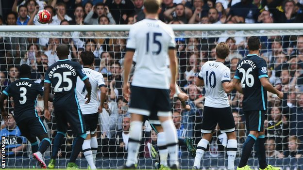Tottenham striker Harry Kane watches as his shot goes in against Manchester City