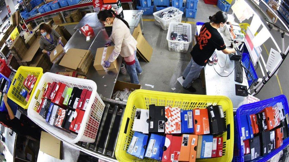 Trabajadores lidiando con paquetes de envío en un almacén en China en 2020.