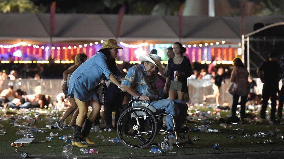 Una mujer empuja a un hombre en una silla de ruedas para ayudarlo a huir.