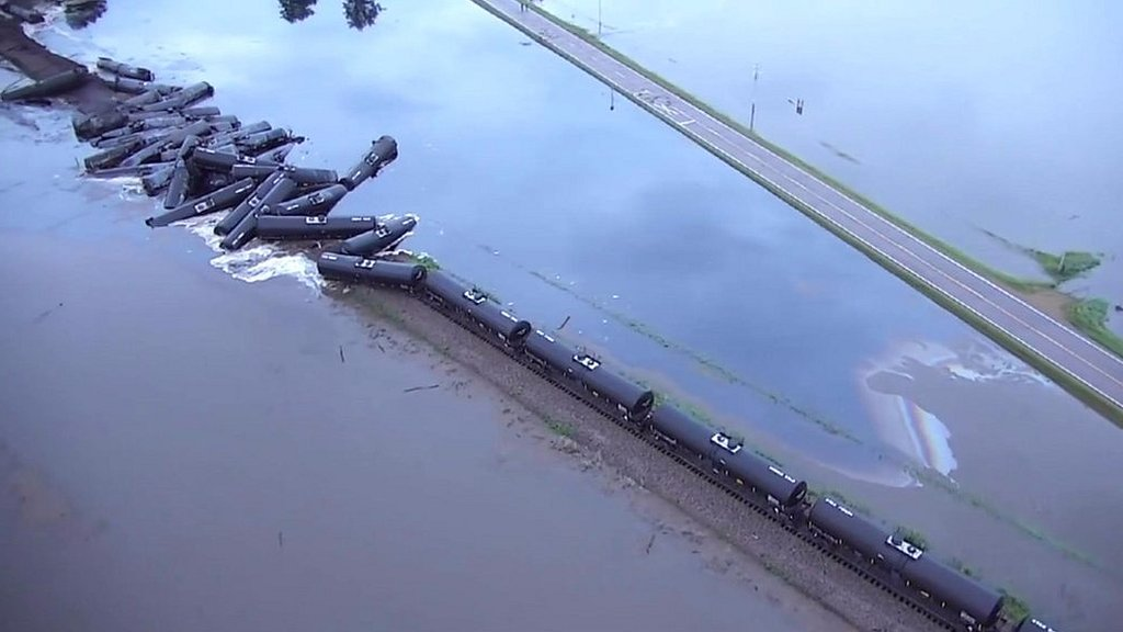 Crude oil pours into river from derailed train in US