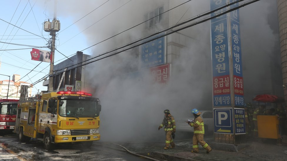 Firefighters try to put out a fire at a hospital in Miryang, southeastern South Korea, 26 January 2018.