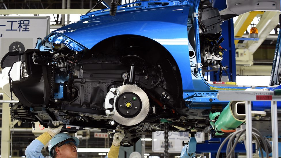 A man works on a Toyota Mirai vehicle on the production line