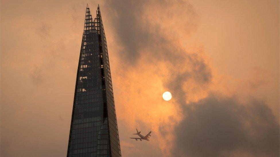 Un avión vuela por el edificio Shard en el centro de Londres, mientras el cielo muestra un color naranja inusual.