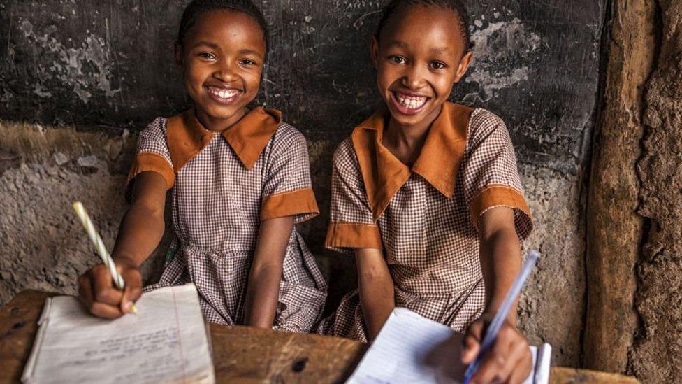Dos niñas con su cuadernos.