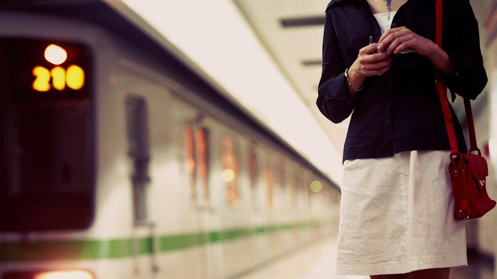 Mulher andando em plataforma de metrô