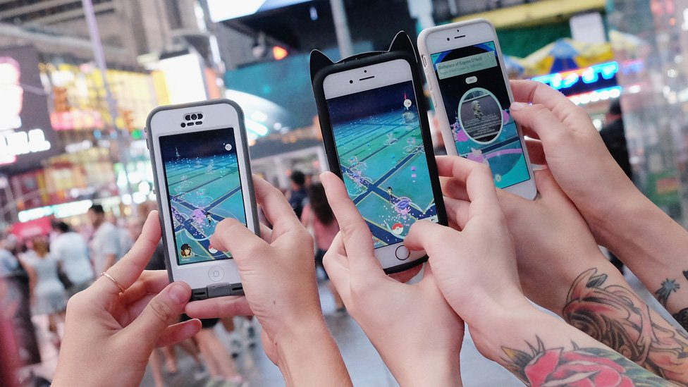 Hands holding phone screens showing Pokemon Go